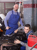 Professional mechanics repairing car Stock Images