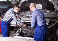 Professional mechanics repairing car. Professional seroius adult mechanics repairing car of client Royalty Free Stock Images