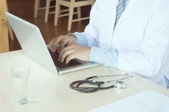 Professional medical doctor in white uniform gown coat working l. Aptop computer royalty free stock photo