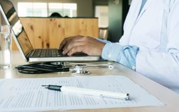 Professional medical doctor in white uniform gown coat working l. Aptop computer royalty free stock images