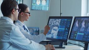 Medical doctors working in hospital office making computer research. Medicine, healthcare and technology concept.