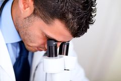 Professional medical man using a microscope Royalty Free Stock Photos