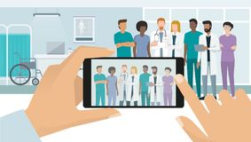 Doctors posing at the hospital. Professional medical staff and doctors posing together in the hospital, a man is taking a picture with a smartphone, subjective Royalty Free Stock Images