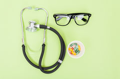 Professional medical treatment. Concept with stethoscope, pills and eyeglasses in closeup stock photo
