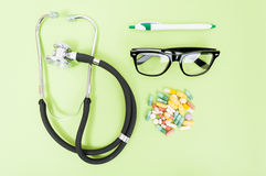 Professional medical treatment. Concept with stethoscope, pills and eyeglasses in closeup royalty free stock image