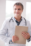 Professional medical worker holding folder with documents. Have an idea. Handsome male person keeping smile on his face and looking aside while going to treat royalty free stock photos