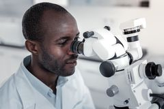 Professional medical worker staring at ocular of microscope royalty free stock photography