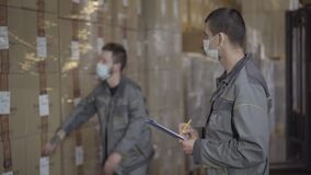 Professional men in face masks checking production in warehouse. Two male Caucasian employees working at factory