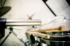 Professional microphone placed close to drums with sticks Stock Photo