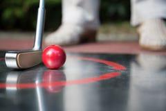 Professional minigolf player starts to hit the ball. Royalty Free Stock Photos