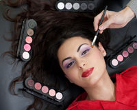 Professional model face makeup routine in studio Royalty Free Stock Photos