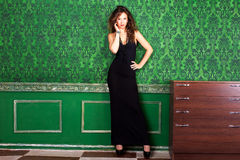 Professional model on a green vintage wall posing in an old room Royalty Free Stock Photo