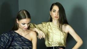 Professional models with chic make-up in dresses on one shoulder poses at photo shoot. At studio stock footage