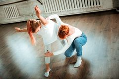Professional modern dance teacher with red hair correcting her student. Legs position. Professional modern dance teacher with red hair wearing jeans correcting royalty free stock photo