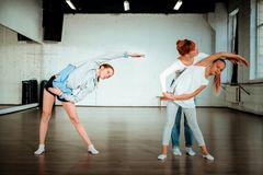 Professional modern dance teacher with red hair helping her student royalty free stock photo
