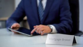 Professional mortgage broker using tablet pc, searching loan offers for client stock photo