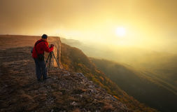 Professional on mountain. Nature photographer takes photos Stock Images