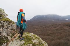Professional mountaineer with a bay of rope stands on a high rock and looks into the distance Stock Images