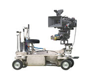 Professional movie camera and dolly isolated. Professional video movie camera used in filmmaking, mounted on a riding dolly.  Isolated on white Stock Photos