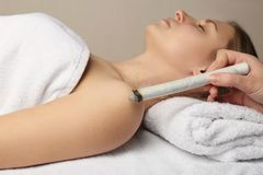 Professional moxa stick in hand of practitioner over woman. `s body stock photo
