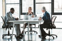 Professional multiethnic business people working together at table. In modern office stock image