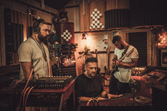 Professional music band recording song in boutique recording studio.  Royalty Free Stock Images
