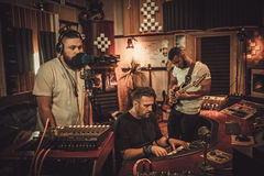 Professional music band recording song in boutique recording studio.  Stock Photos
