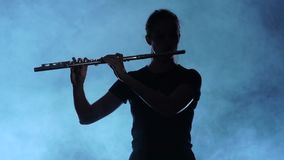 Professional musician female playing on flute. Smoky studio, slow motion. Professional musician female playing on flute, brass wind instrument, musician plays stock footage