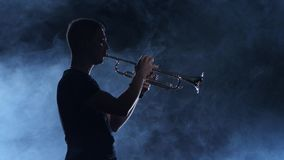 Professional musician man playing on trumpet. Smoky isolated studio, silhouette stock video footage
