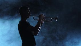 Professional musician man playing on trumpet. Smoky silhouette, slow motion stock footage
