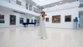 Professional musician performs with wooden violin in a museum. 4K stock video footage