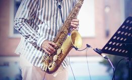 A professional musician plays a jazz composition on a vintage gold saxophone. A professional musician, dressed in a striped shirt and white trousers, plays a royalty free stock images