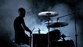 Professional musician plays music on drums . Smoky background. Side view. Silhouette. Back light. Slow motion stock video footage