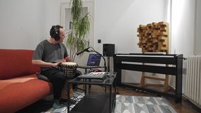 Musician playing djembe drum instrument in home music studio. Professional musician recording djembe drum instrument in digital studio at home.  He is