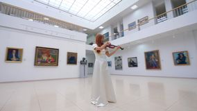 Professional musician in white dress plays violin in museum with paintings. 4K stock video