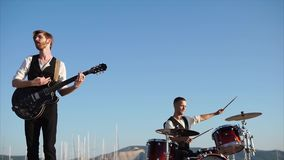 Professional musicians play on instruments, called drum set and rhythm guitar stock footage