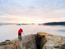Professional photographer above clouds. Man takes photos with camera on tripod on rocky peak. Professional nature photographer above clouds. Man takes photos Royalty Free Stock Images