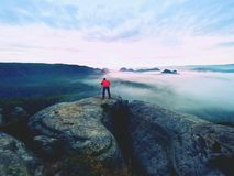 Professional photographer above clouds. Man takes photos with camera on tripod on rocky peak. Professional nature photographer above clouds. Man takes photos Stock Image