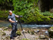 Professional nature photographer with camera on tripod. Professional nature photographer in a canyon by the river Stock Image