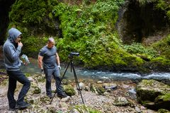Professional nature photographer with camera on tripod. Professional nature photographer in a canyon by the river Stock Photo