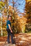 Professional photographer shooting autumn colors. Professional nature photographer with camera on tripod shooting colorful autumn forest Royalty Free Stock Images