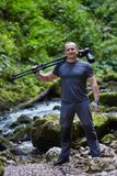 Professional nature photographer with camera on tripod. Professional nature photographer in a canyon by the river Stock Photography