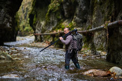 Professional nature photographer in the gorge. Professional nature photographer crossing the river with his tripod and camera Royalty Free Stock Photography