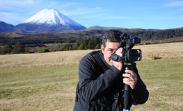 Professional nature, wildlife and travel videographer/photograph. Professional nature, wildlife and travel videographer filming Mount Ngauruhoe outdoors during Stock Photography