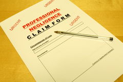 Professional Negligence Claim Form. A Professional Negligence Claim Form on a table with a pen placed on top Stock Images