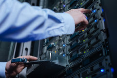 Professional nice engineer working with new technologies. Modern telecommunications. Professional nice male engineer standing in front of the server rack and Stock Photos