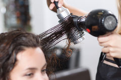Professional nice hairdresser holding hairdryer Royalty Free Stock Image