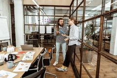 Professional nice men standing in the office. At the workplace. Professional nice men standing in the office while discussing their projects royalty free stock images