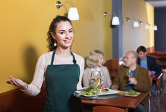 Professional nippy with tray posing at table. Professional positive smiling nippy with tray posing at table of senior customers Stock Photo