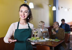 Professional nippy with tray posing at table. Of senior customers Royalty Free Stock Photography